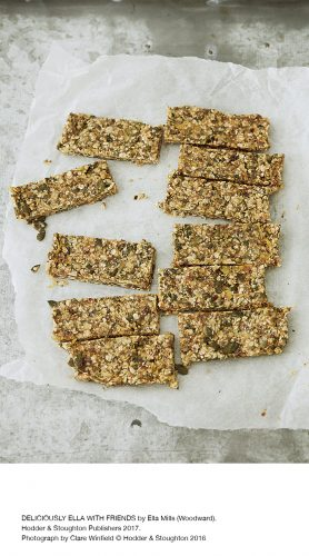 white background crunchy batch of rectangular bars that look like flapjacks oats and fruit on baking paper and marble work surface golden colour and textured