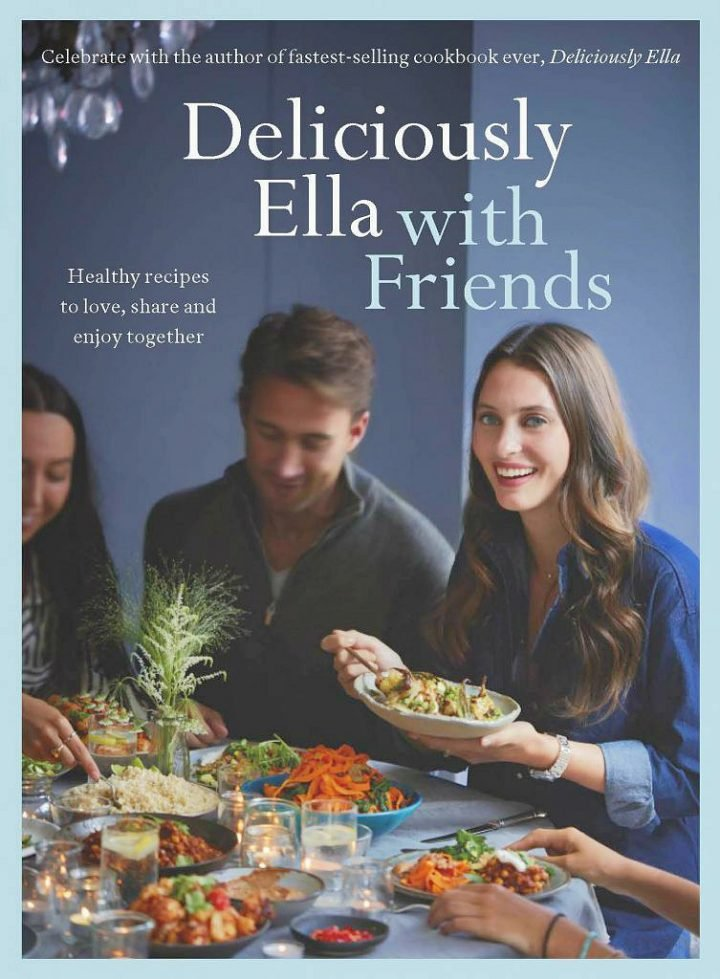 book cover three people around a table sharing food young woman with long hair smiling lots of healthy and colourful food on the table one man and two women