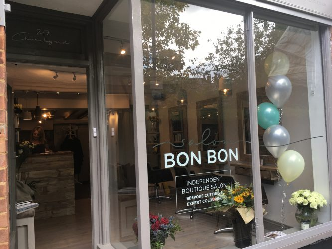 Lovely window and shop front with coloured balloons and lots of glass and a reflection of trees and a church with warm and inviting lighting
