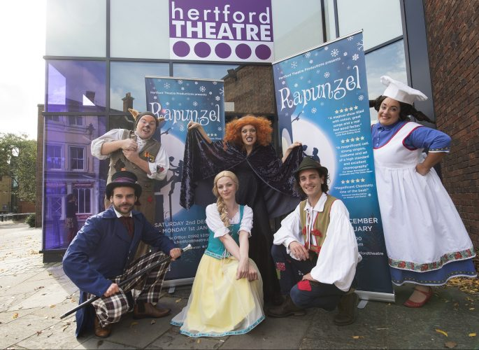 Exterior of Herford Theatre with glass and brick and characters in pantomime costume for Rapunzel wearing colourful dresses and hats