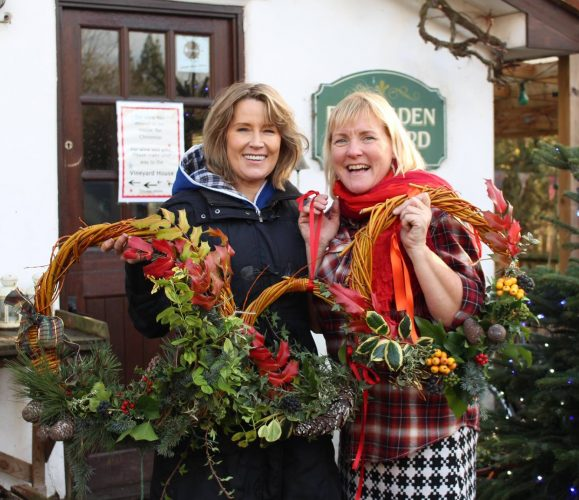 Christmas wreaths with lots of greenery and holly and ribbons with two women smiling standing outside a pretty Hertfordshire house in a leafy garden