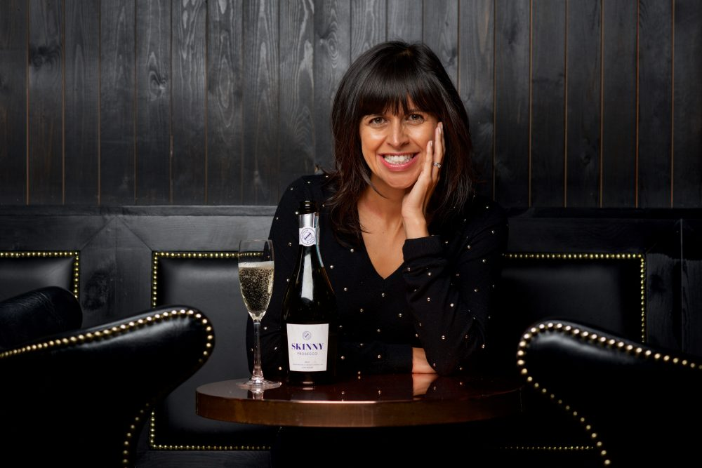 Entrepreneur with bottle of Skinny Prosecco in a dramatic interior bar with or restaurant with black wooden panelling and black leather armchairs