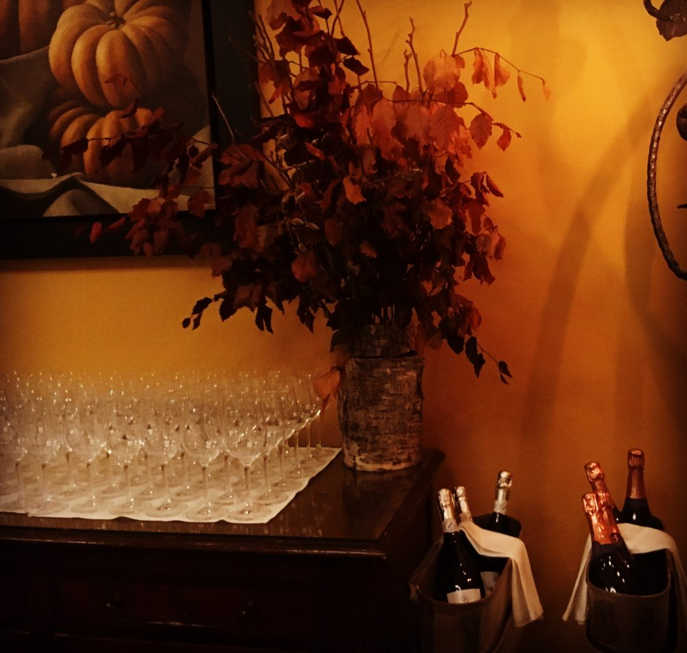 Autumn colour in restaurant interior with wine glasses, bottles of prosecco, warm colours and autumn leaves