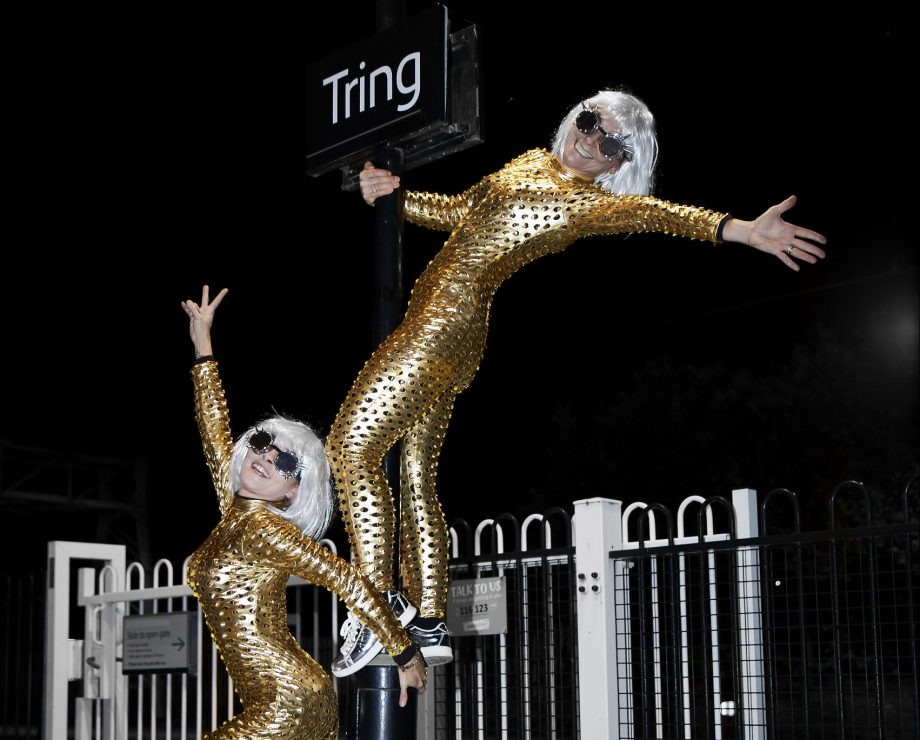 Two women wearing silver wigs, sunglasses, and gold bodysuits standing waving their arms at Tring railway station and ready to party