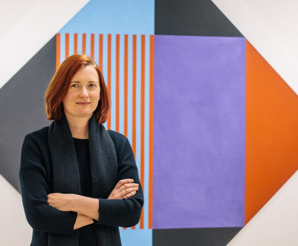 woman shoulder length auburn hair crossed arms dark clothes artwork purple and orange and blue on white wall