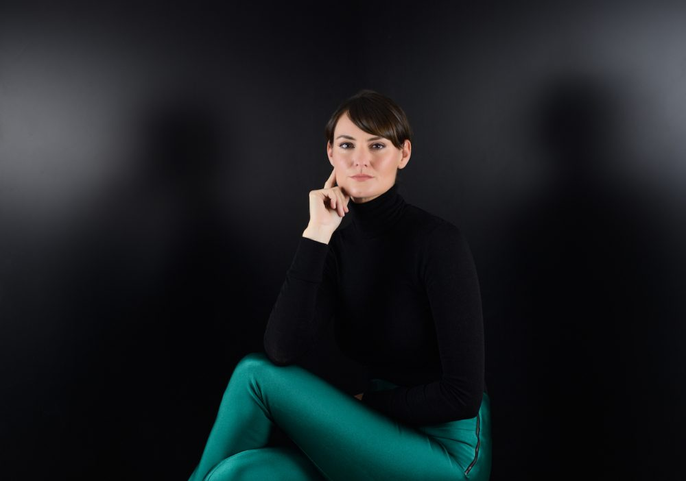 black background woman dark short hair black jumper jade green trousers
