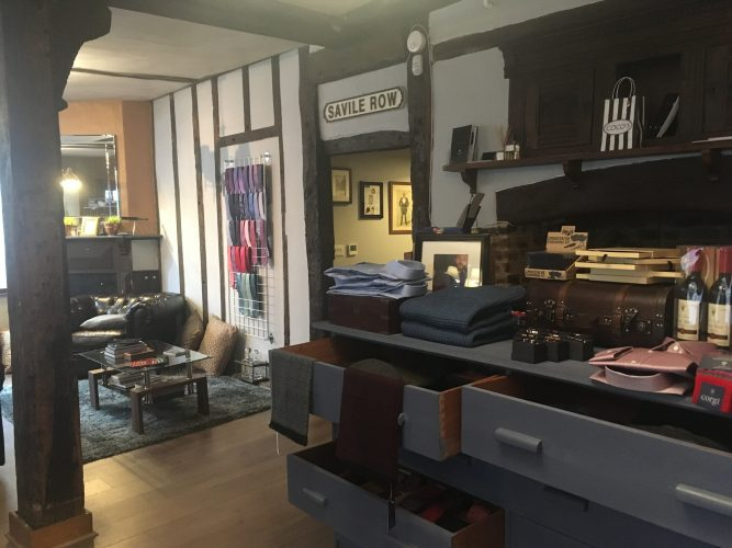 old building mirror chest of drawers grey paint rack on white wall men's ties red pink purple blue bottles of wine on dresser cufflinks wooden floor exposed beams and dark timber on white walls
